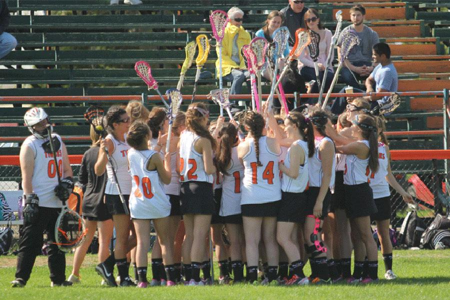 Girls lacrosse forms a huddle before a home game.