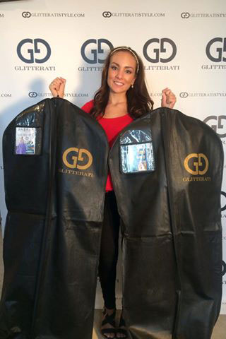 Gale holding up her dresses to be worn at the pageant.