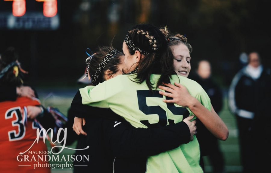 Seniors Hailey Allen, Paige Laverriere, and Taylor Wildes hug after the game. Photo courtesy of Maureen Grandmaison Photography.
