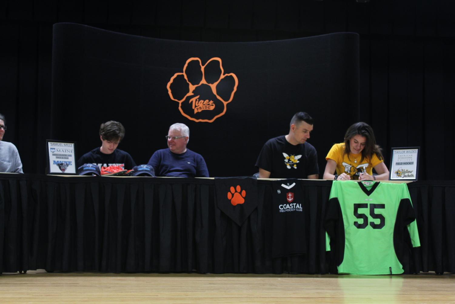 Seniors Taylor Wildes (right) and Sam Mills (left) sign their commitment letters with their parents on April 24. GRACE LAVERRIERE/The Roar